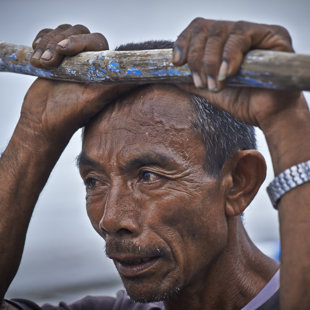 Fisher man resting at hes outrigger, Eastern Java
